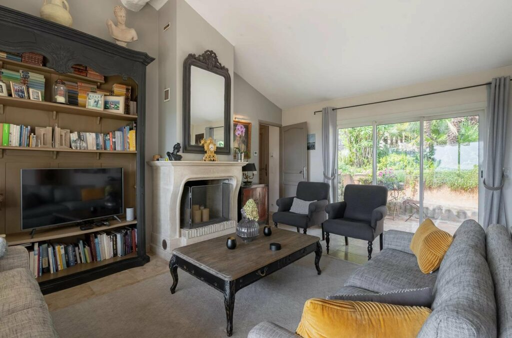 living room with grey couch and dark wood table in center with fireplace