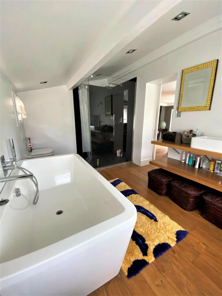bathroom with large white tub and yellow and black rug