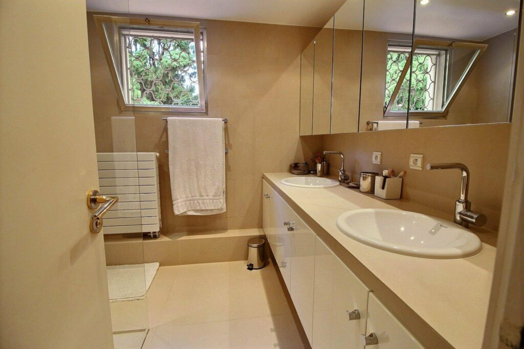 bathroom with beige tile walls and white tile floors
