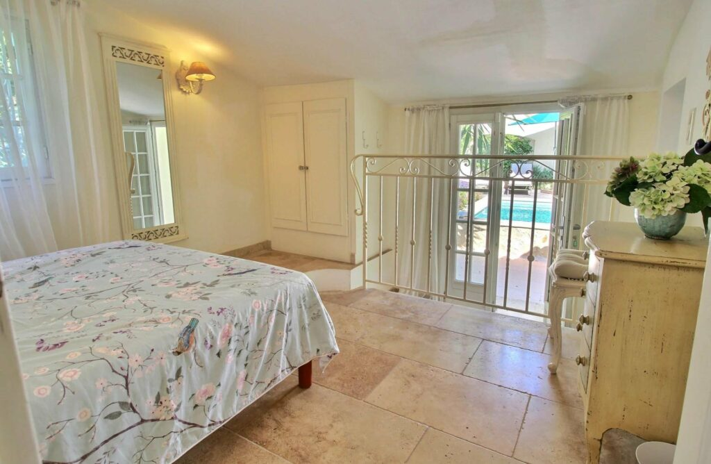bedroom with tile floors and queen size bed and access to backyard