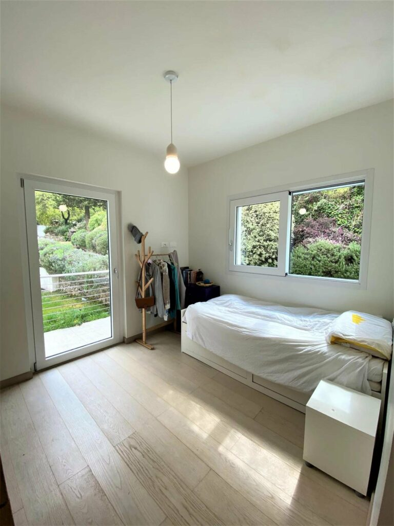 bedroom with pale wood floors and white single bed and large glass sliding door