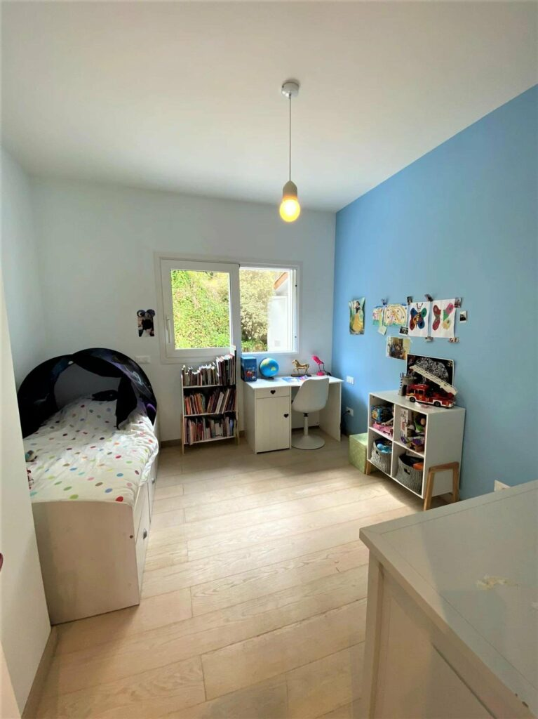 childrens room with wood floors and blue wall and toys around bed