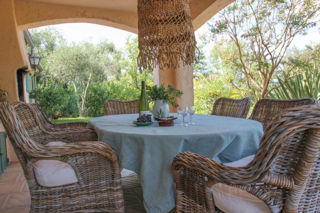 backyard of provencal villa with round table and woven detailing