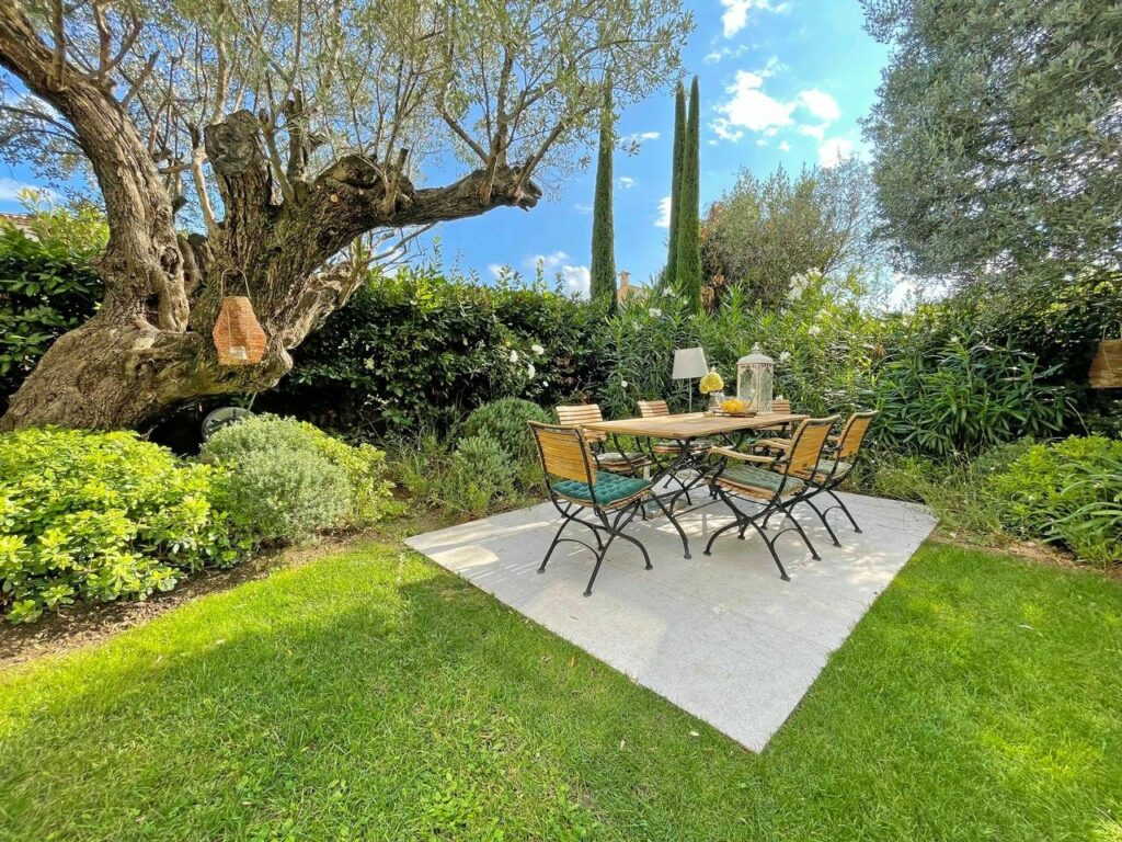 backyard with table surrounded by garden plants