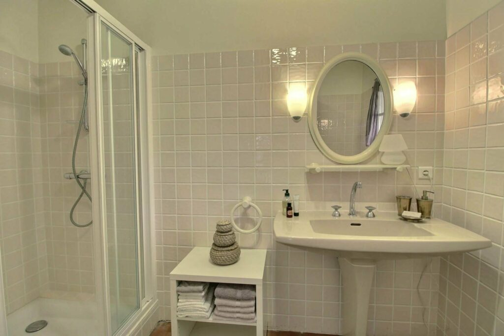 all white classic style bathroom with oval shaped mirror