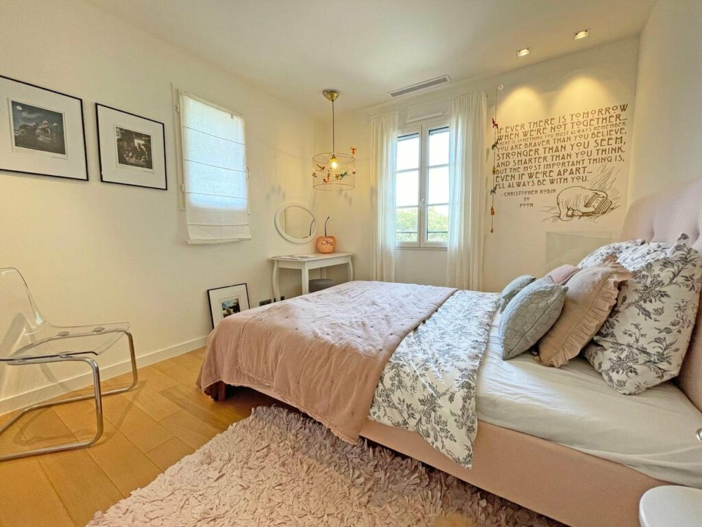 bedroom with light pink bedding and textured rug underneath