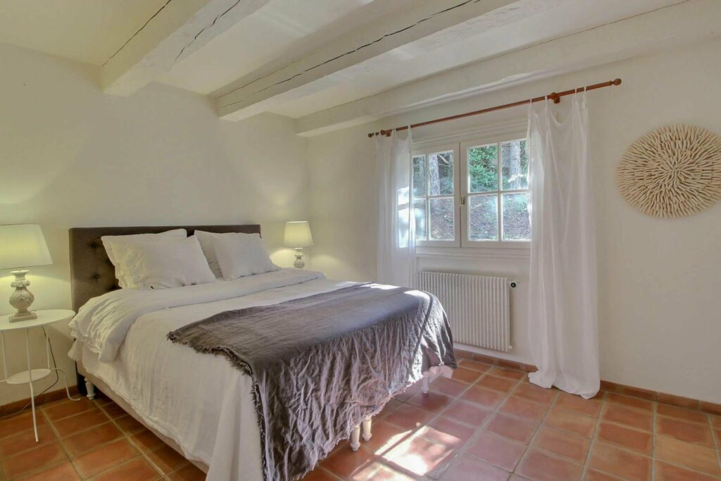 bedroom with rustic tile floors and small window