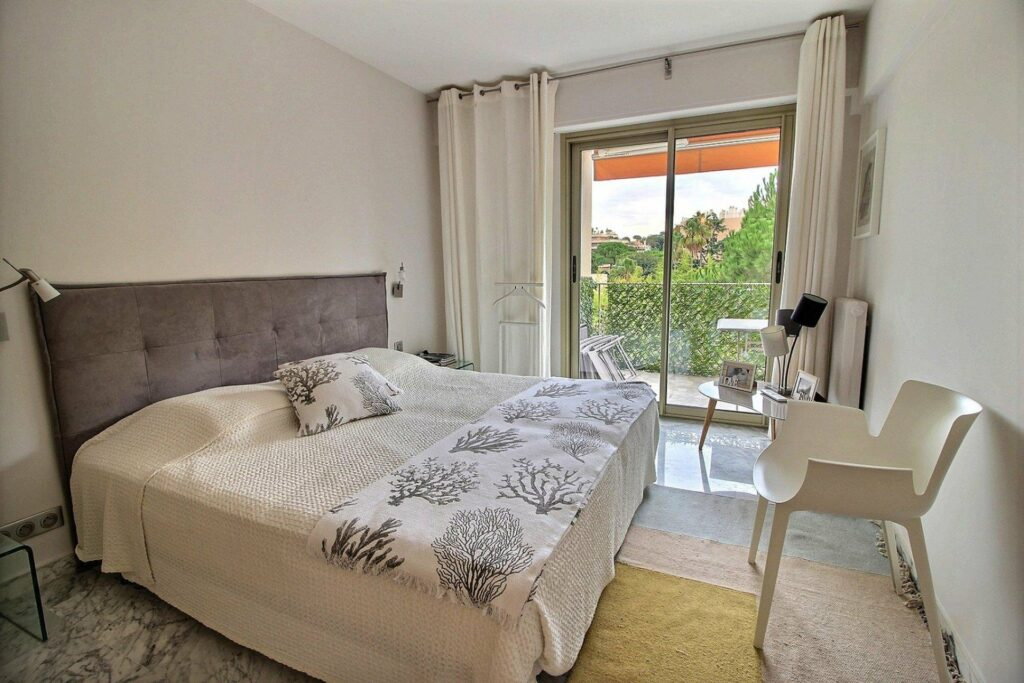 bedroom with white and grey bedding in apartment in south france