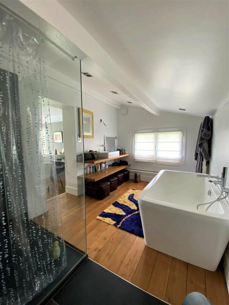 bathroom with standing glass shower in modern villa with exposed white beams