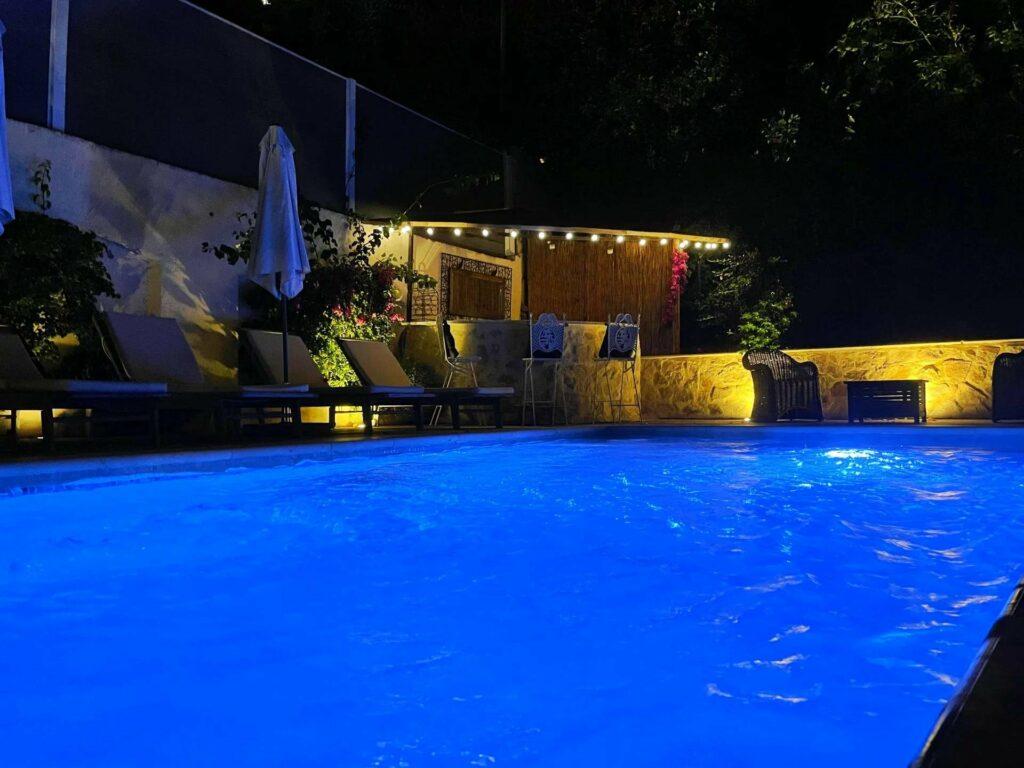 view of villa pool at night lit up