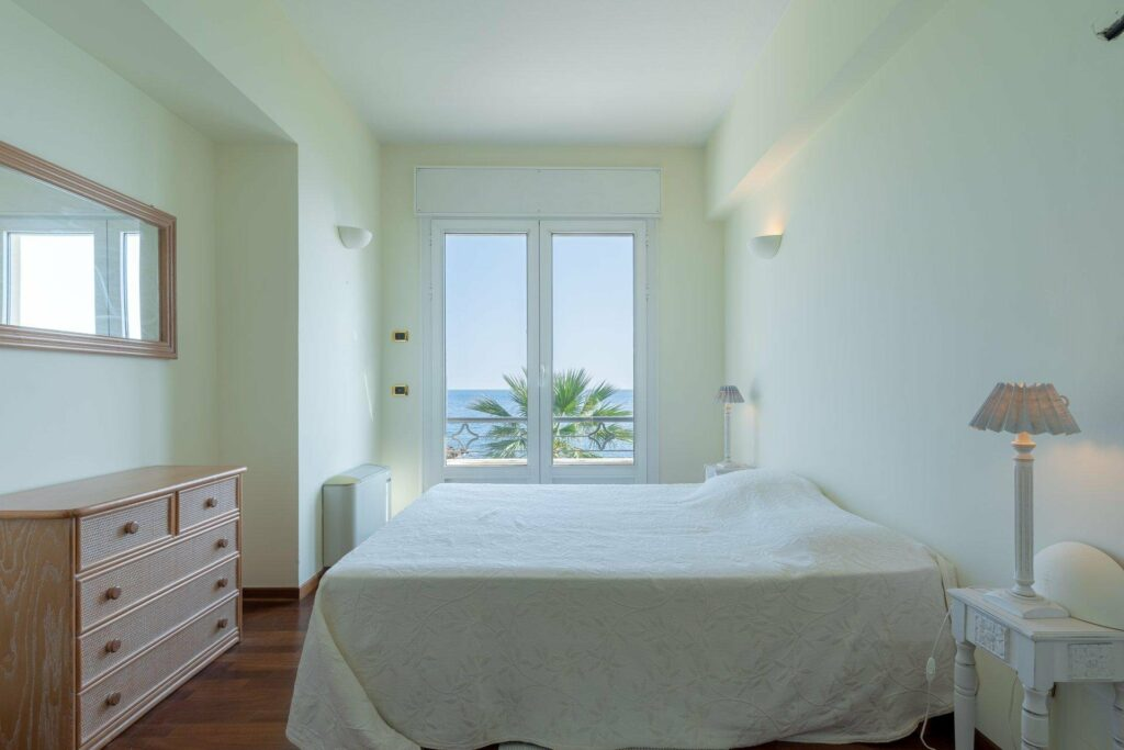 bright bedroom with sea view from small window