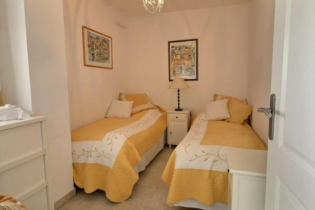 bedroom with two single beds with yellow and white bedding