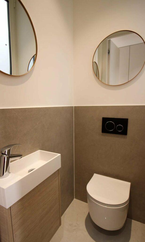 modern bathroom with grey tile walls and circular mirrors