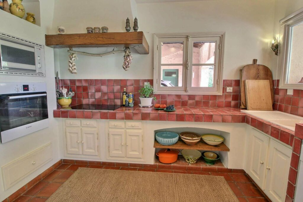 provencal kitchen with red tile walls